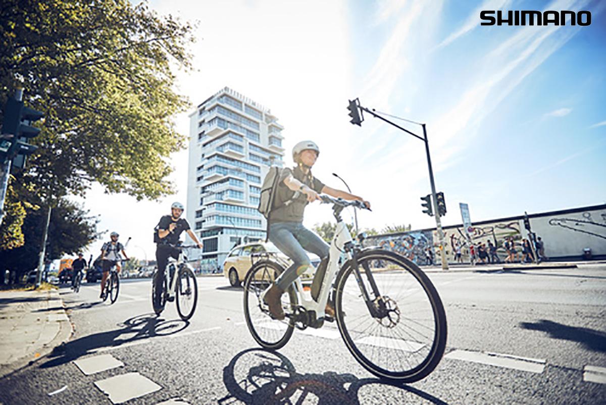 Un ciclista pedala in sella a una e-bike all'interno della città