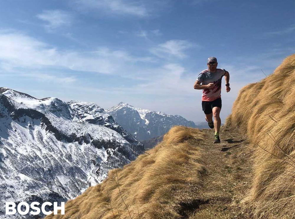 Un trail runner corre sulla cresta di una montagna