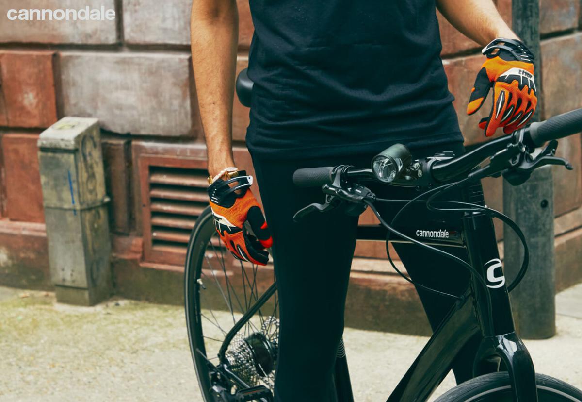 Cislista uomo posa accanto alla sua ebike da fitness Cannondale 2021