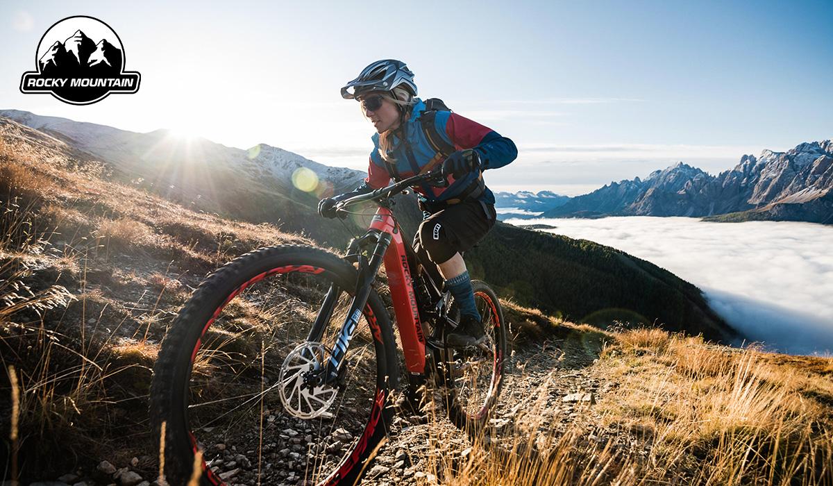 Una ragazza pedala insieme ella ad una nuova emtb full Rocky Mountain 2021