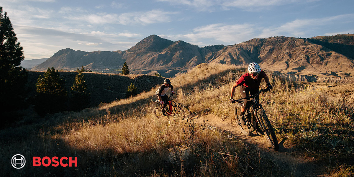 Due ragazzi affrontano un trail in salita in sella a una mountain bike elettrica