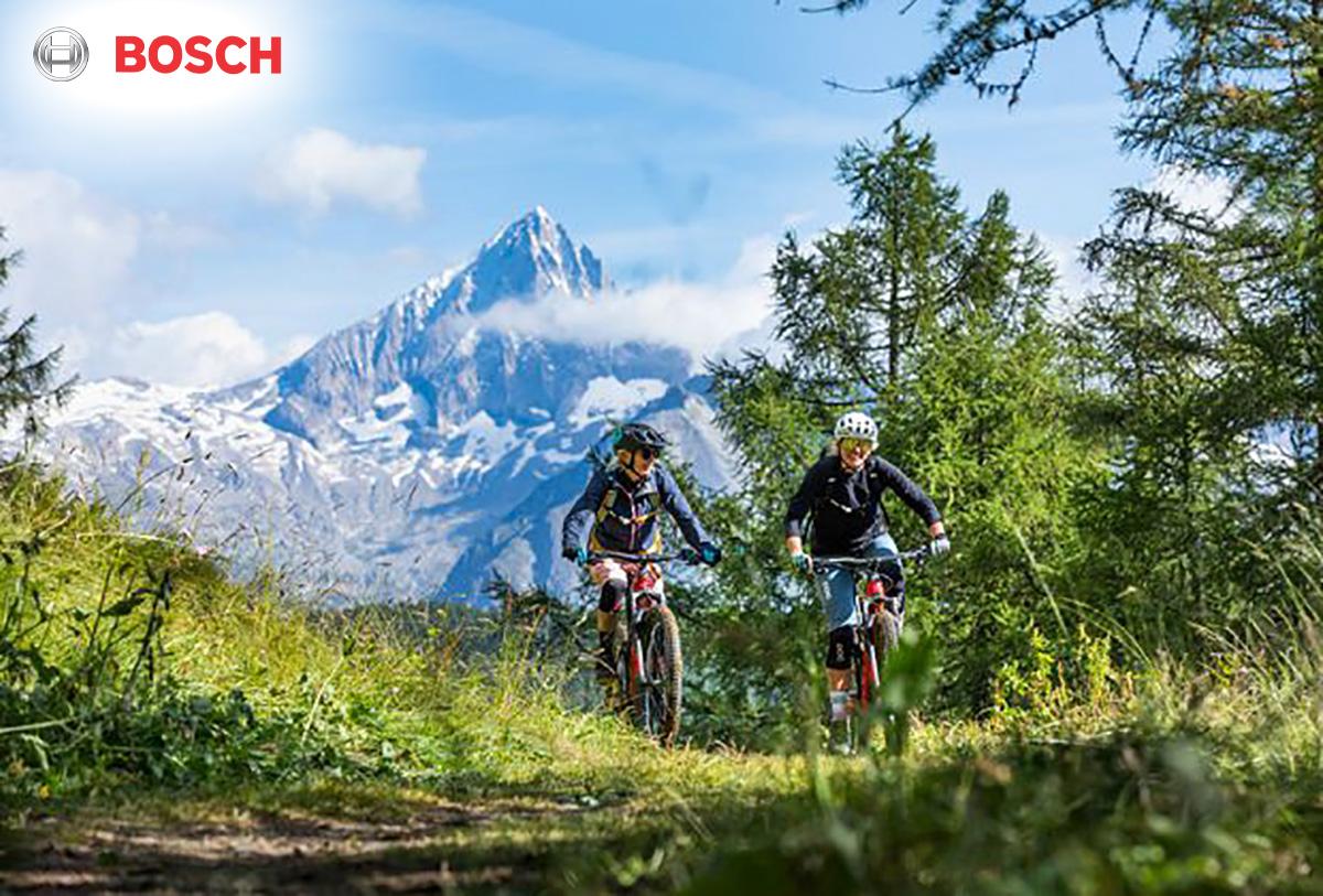 Due rider pedalano in sella a una e-bike con una montagna innevata sullo sfondo