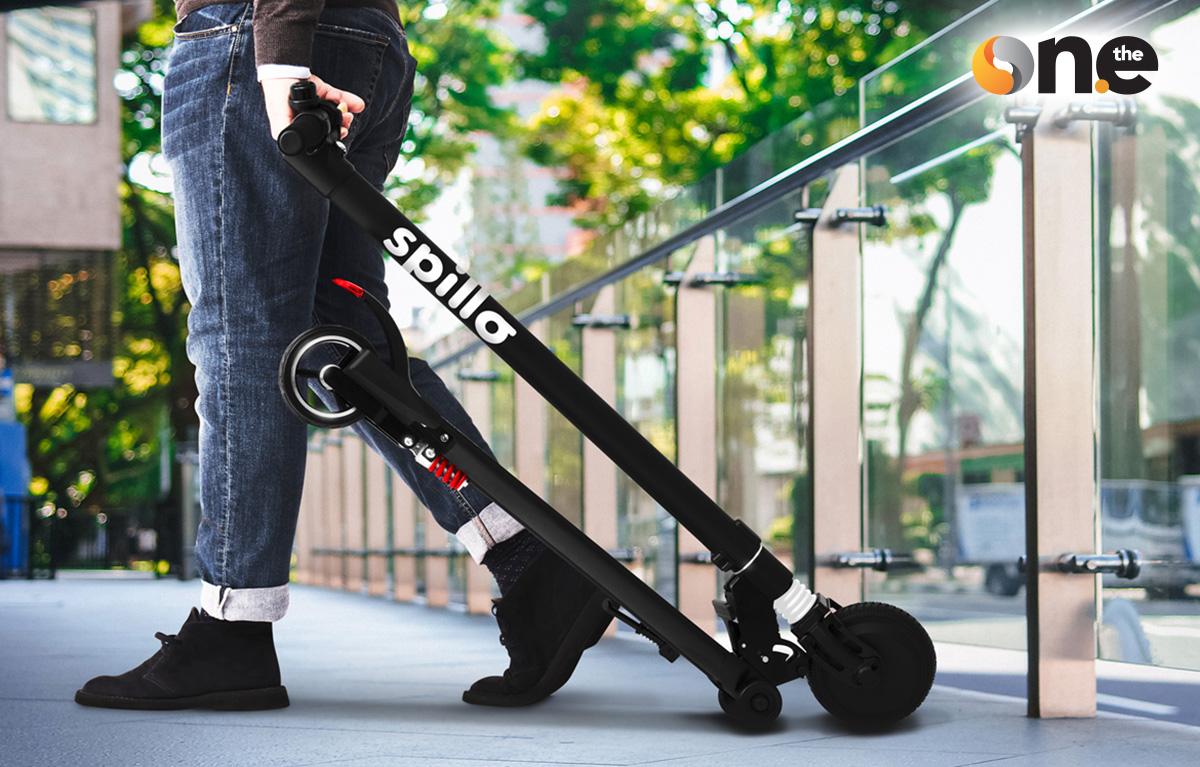 Un uomo cammina trasportando il nuovo monopattino elettrico The One Spillo 2021