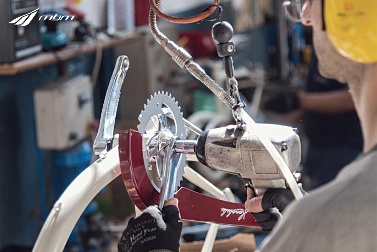 Un operaio assembla una bicicletta nello stabilimento Cicli Mbm