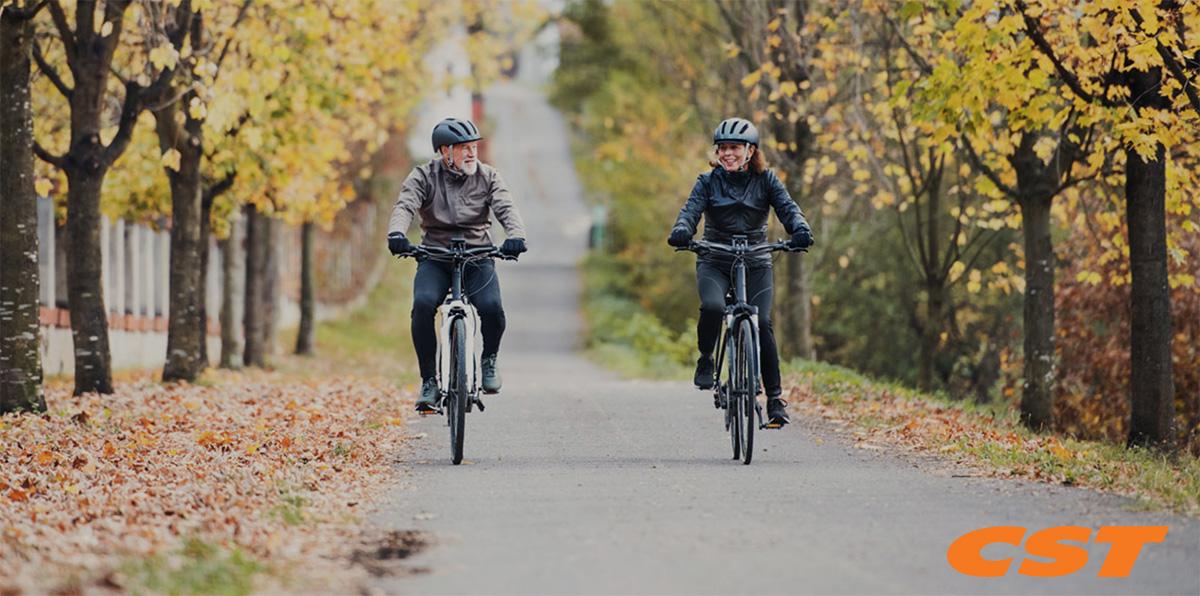 Una coppia di anziani pedala per un viale alberato con le loro ebike che montano pneumatici CST