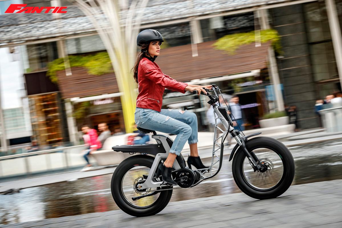 Una ragazza pedala in città con una ebike urban Fantic 2021