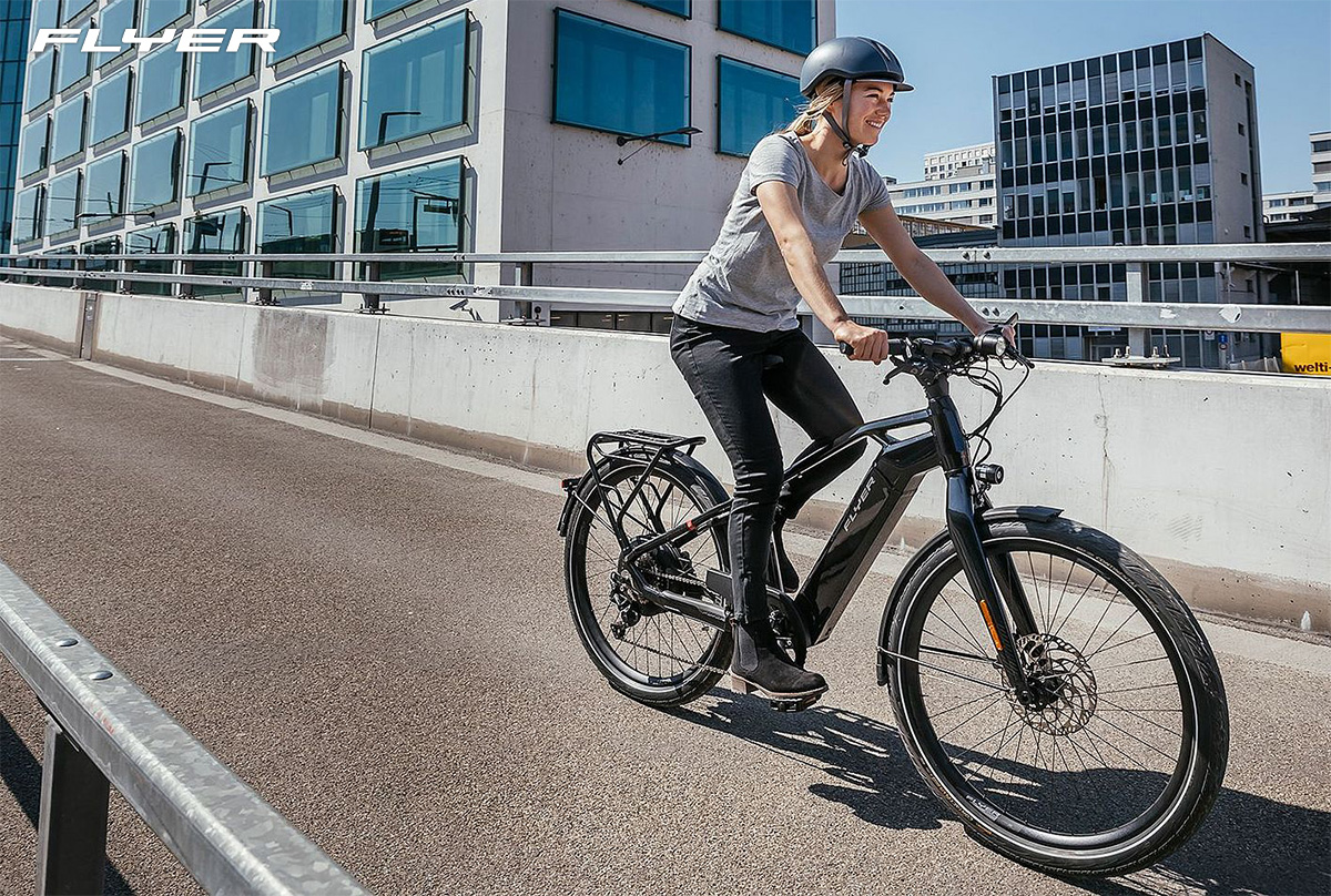 Una donna pedala per la città con una nuova ebike Flyer 2022