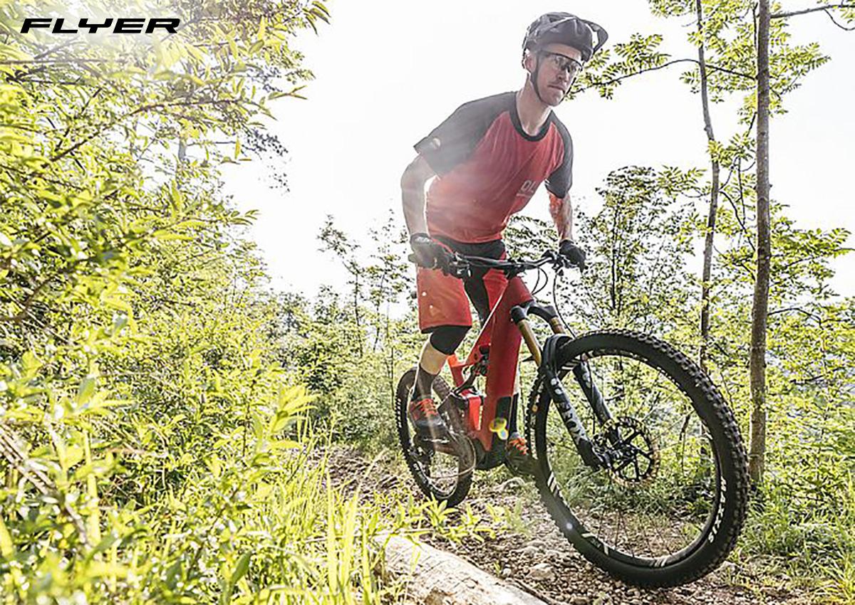 Un rider pedala tra le piante con una nuova mtb elettrica Flyer 2022