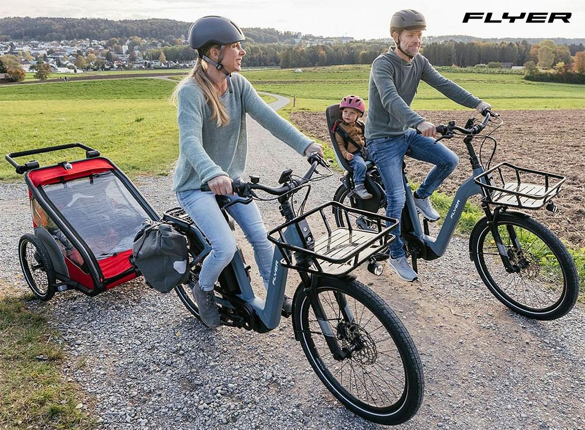 Due genitori trasportano i loro figli con le nuove ebike Flyer Gotour3 2022 equipaggiate con trasportini
