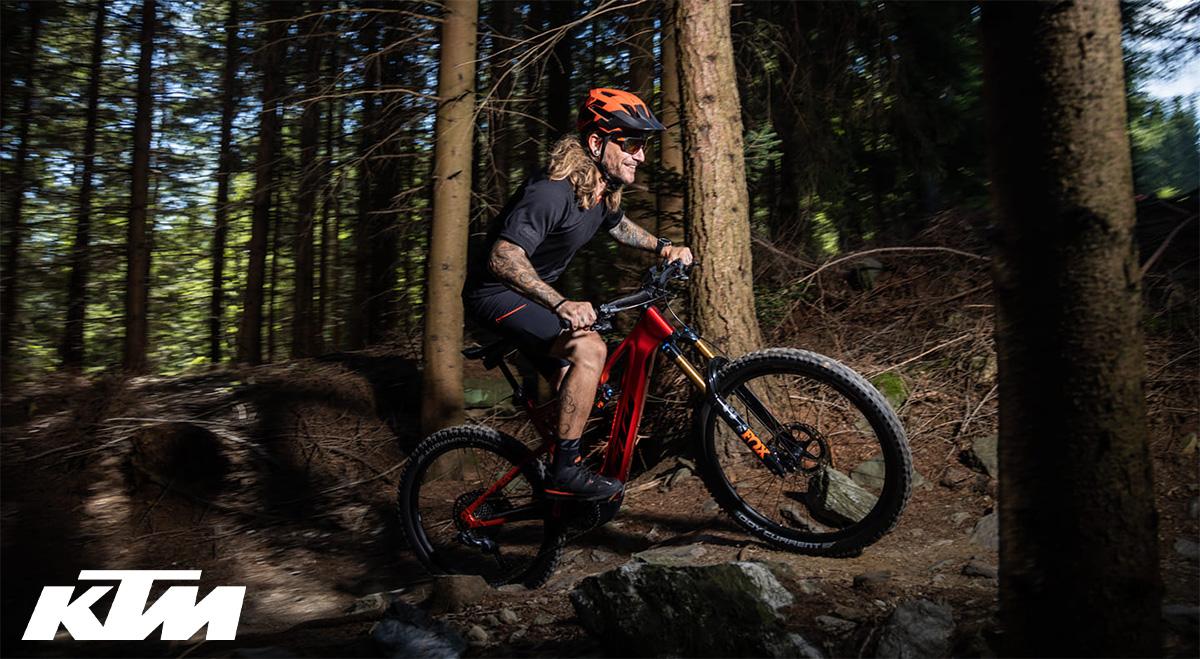 Un rider pedala nel bosco con la nuova emtb KTM Macina Prowler 2022