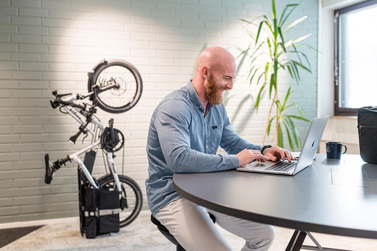 Un uomo lavora in ufficio con la propria ebike pieghevole Tern parcheggiata contro il muro