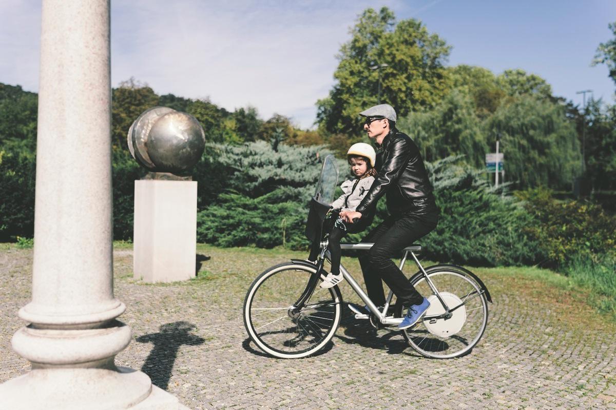 Un adulto e un bimbo a cavallo di una bici elettrica