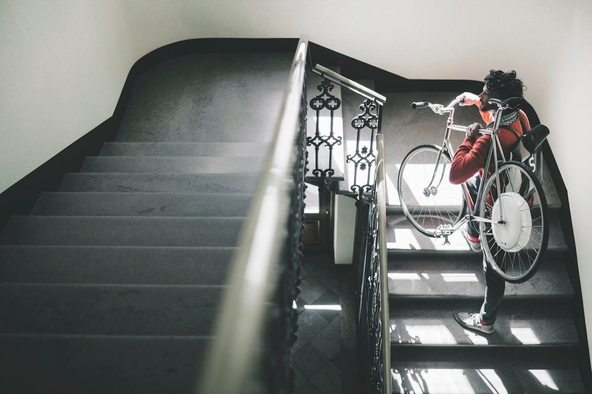 Un ciclista si posta la bici in spalla su per le scale