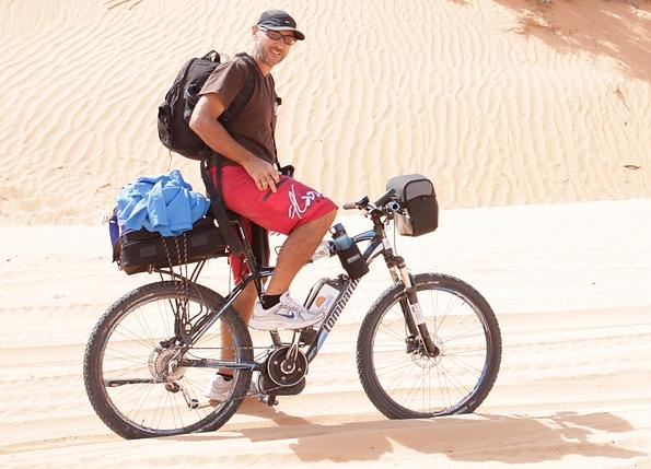 Ciclista in sella a ebike nella sabbia del deserto