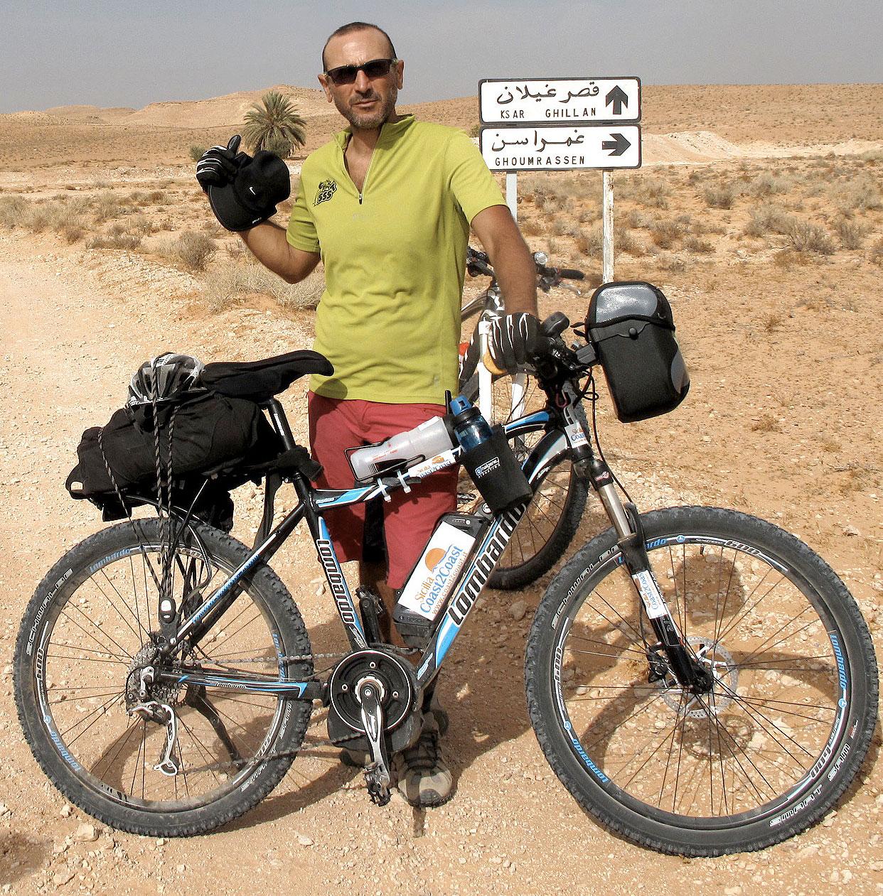 Ciclista nel deserto con una bicicletta elettrica